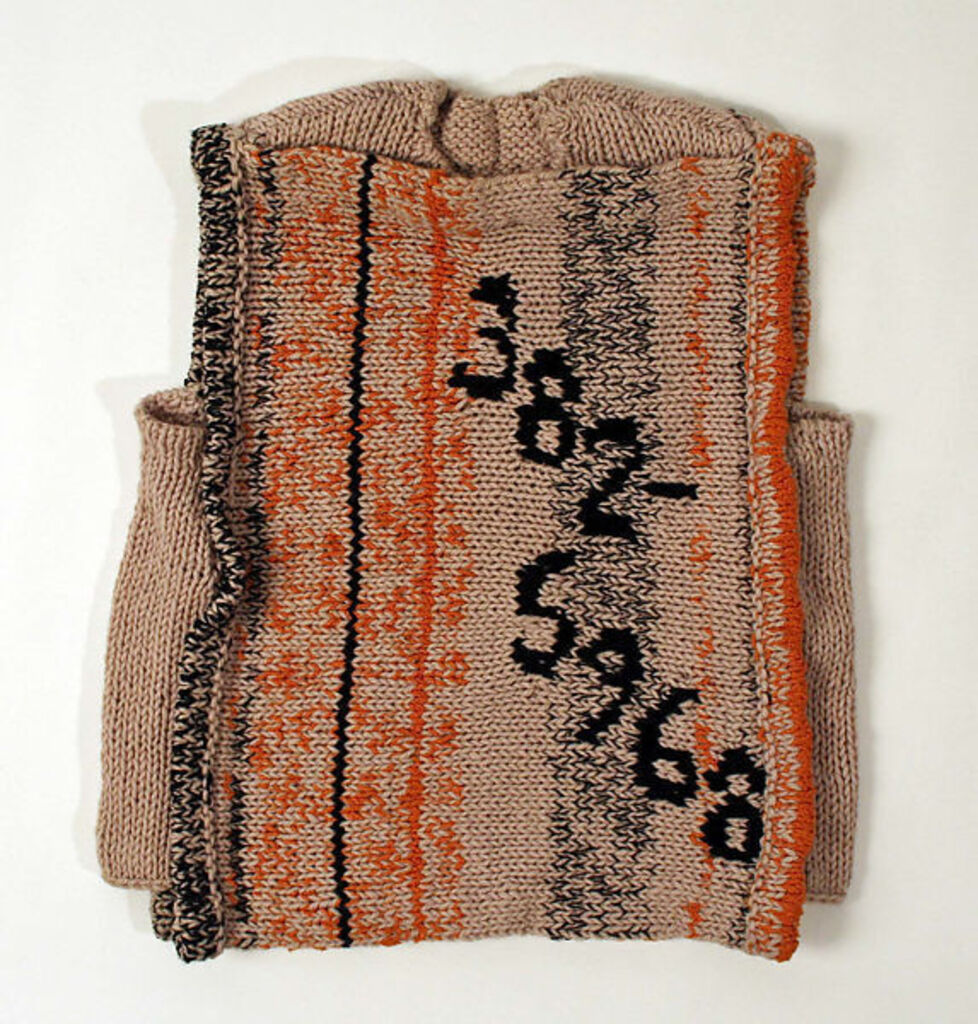 Beige, orange and black knitted sweater with the numbers 382-5968 stitched on