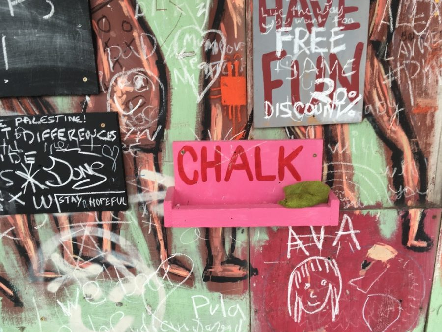 Colourful graphitti wall with messages involving discounts, Free Palestine, doodles. It has a prominent pink shelf in centre that reads CHALK. On it is a green sponge, but no chalk.