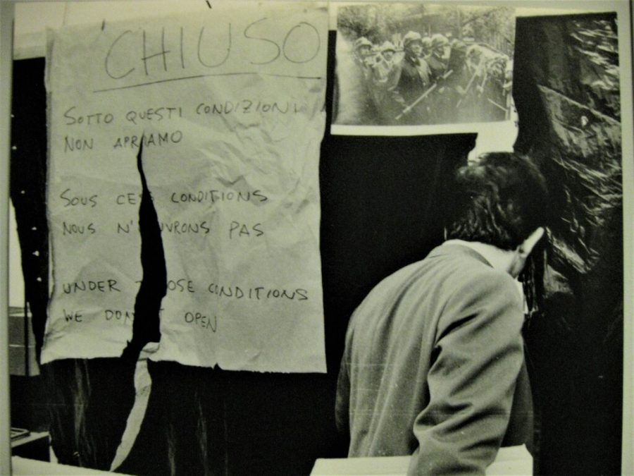 """Black and white photo of back of man walking past a ripped handwritten sign which reads, """"CHIUSO. Sotto questi condizioni non apriamo..."""" A photograph of riot police holding battons hangs next to it."""